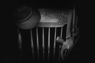 Čierny klobúk (Black Hat) zavesený na operadle stoličky s opaskom v ktorom je revolver